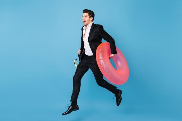 Portrait En Pied De L'homme En Tenue D'affaires En Cours D'exécution Sur L'espace Bleu Avec Cercle Gonflable Rose. Photo gratuit