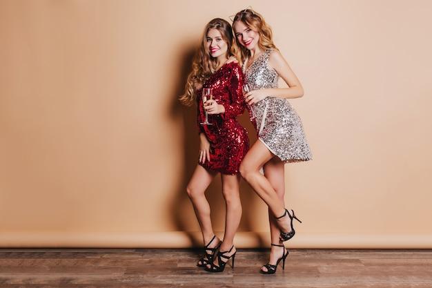 Portrait En Pied De Superbes Femmes En Tenue De Luxe Dansant Ensemble à La Fête Du Nouvel An Photo gratuit