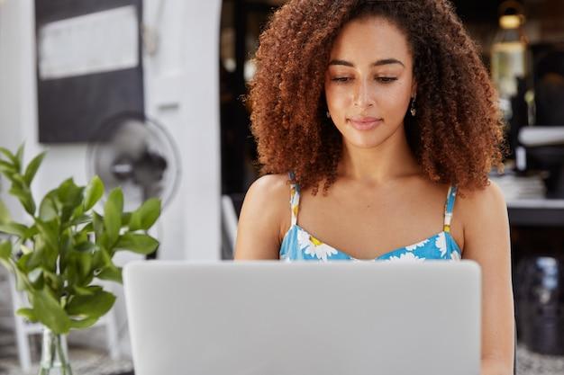 Portrait De Pigiste Afro-américaine Occupée Axée Sur L'ordinateur Portable, Satisfait Du Succès Des Affaires En Ligne, Travaille Dur Pour Réussir Photo gratuit