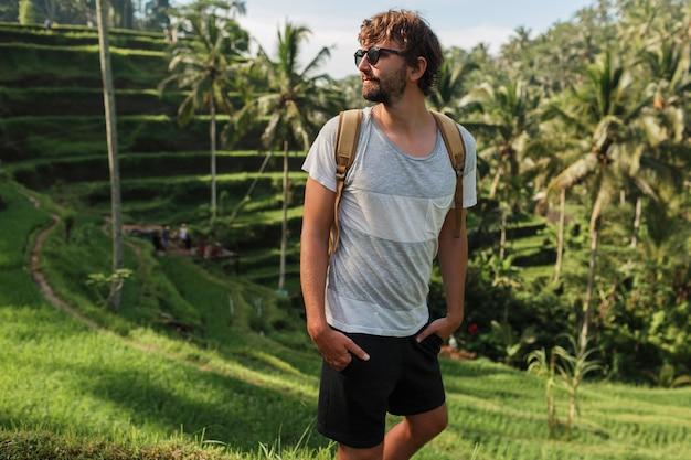 Portrait En Plein Air De Bel Homme De Voyage Avec Sac à Dos Marchant Sur La Terrasse De Montée à Bali. Photo gratuit