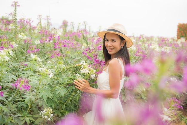 Portrait en plein air d'une belle femme asiatique d'âge moyen. jolie fille dans un champ avec des fleurs Photo gratuit