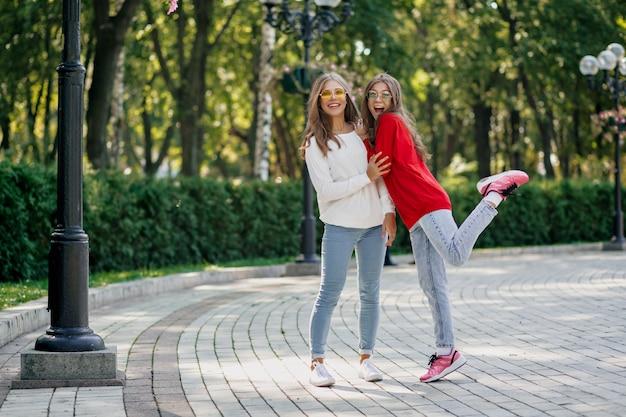 Portrait En Plein Air De Deux Filles Heureuses Assez Sympathiques S'amusant Et Marchant Ensemble Après Les études Dans La Ville, Journée Ensoleillée, Bonnes Vraies émotions, Humeur Drôle Photo gratuit