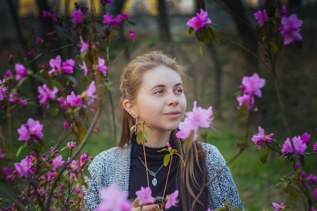 Portrait En Plein Air De Femme Européenne Dans Un Buisson De Fleurs Roses Et Violettes Dans Le Parc Du Printemps Photo Premium