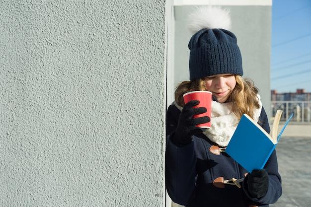 Portrait en plein air hiver de jeune étudiante avec livre Photo Premium