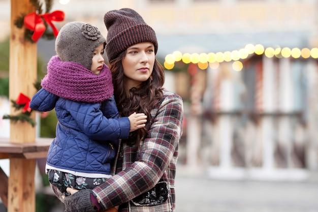 Portrait en plein air de jeune femme et petite fille à la décoration de noël en ville Photo Premium