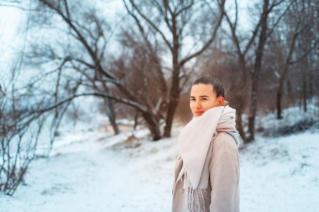 Portrait En Plein Air De Jeune Fille Dans Le Parc En Journée D'hiver, Portant Un Foulard Et Un Manteau, Sur Fond D'arbres. Photo Premium