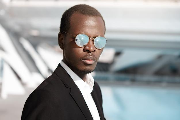Portrait En Plein Air De Séduisant Homme D'affaires Afro-américain Confiant De 30 Ans Portant Un Costume Formel Noir Et Des Lunettes De Soleil Rondes élégantes Photo gratuit