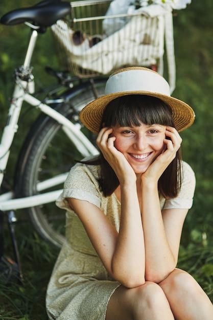 Portrait en plein air de séduisante jeune brune au chapeau sur un vélo. Photo gratuit