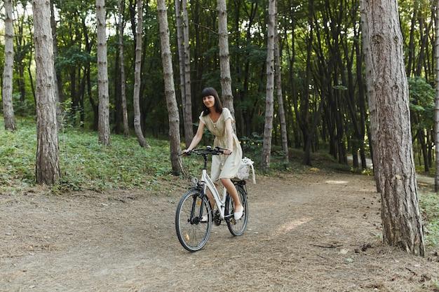 Portrait en plein air de séduisante jeune brune sur un vélo. Photo gratuit