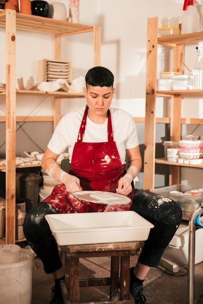 Portrait d'une potière peignant les petites tuiles dans l'atelier Photo gratuit
