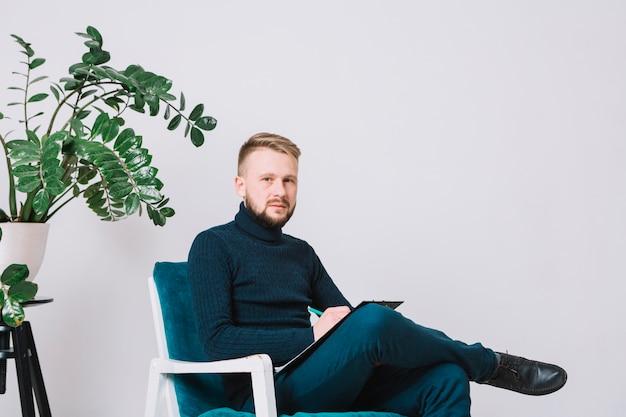 Portrait D'un Psychologue Assis Sur Une Chaise Avec Le Presse-papier Et Un Stylo Contre Le Mur Blanc Photo gratuit