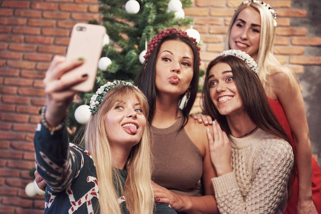 Portrait De Quatre Fille Souriante Avec Corolle Sur La Tête Faire Photo Selfie. Sentiment De Nouvel An. Joyeux Noël Photo Premium