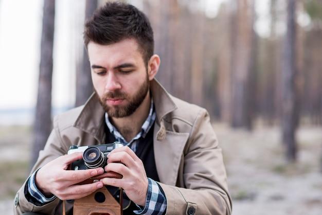 Portrait d'un randonneur ajustant l'objectif de la caméra Photo gratuit