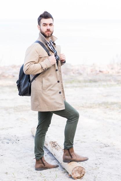 Portrait d'un randonneur avec son sac à dos debout avec son pied sur le journal Photo gratuit