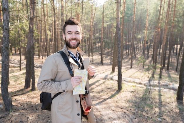 Portrait d'un randonneur souriant tenant une carte générique dans la forêt Photo gratuit