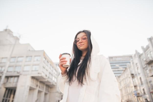 Portrait De Rue D'une Fille élégante Dans Des Vêtements Décontractés, Debout Dans La Rue Avec Une Tasse De Café à La Main, Regarde La Caméra Photo Premium