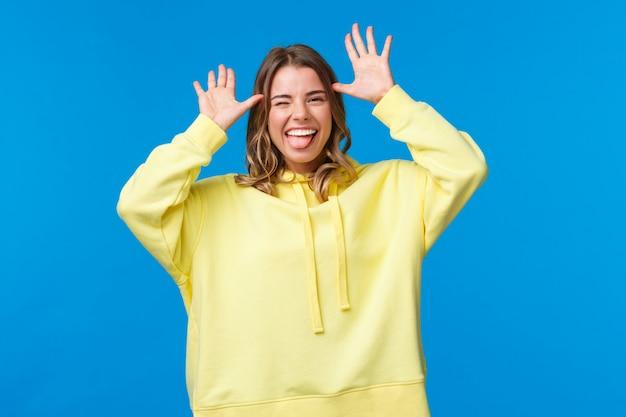 Portrait De Séduisante Fille Blonde Caucasienne Insouciante S'amuser, Montrant Attraper Moi Si Vous Le Pouvez, Grimace Ludique Avec Les Mains Près De La Tête, Bâton De Langue Et Souriant, Photo Premium