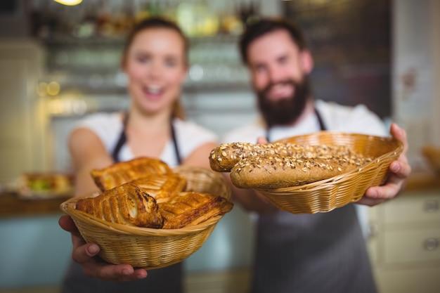 Portrait de serveur et serveuse tenant un panier de pain Photo gratuit