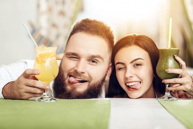 Portrait souriant couple amoureux buvant des cocktails Photo Premium