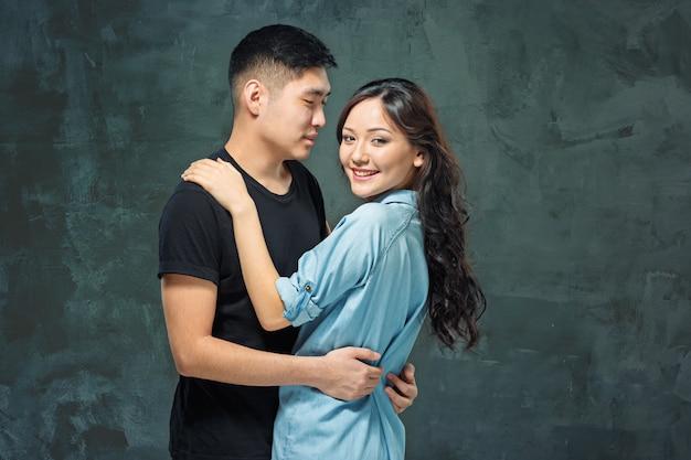 Portrait De Souriant Couple Coréen Sur Un Mur Gris Photo gratuit