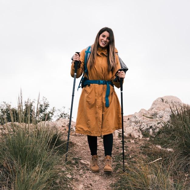 Portrait, de, a, souriant, femme, randonneur, tenue, bâton randonnée, regarder appareil-photo Photo gratuit