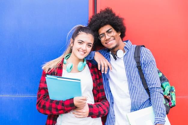 Portrait De Souriant Jeune Couple à La Recherche D'appareil Photo Contre Un Mur Lumineux Photo Premium