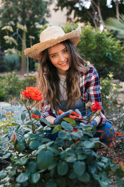 Portrait souriant d'une jeune femme coupant la belle rose adulte avec des cisailles Photo gratuit