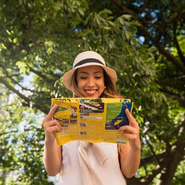 Portrait souriant, de, jeune femme, debout, dans parc, lecture carte Photo gratuit