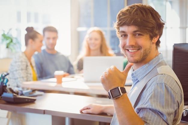 Portrait de souriant jeune homme d'affaires avec des collègues Photo Premium