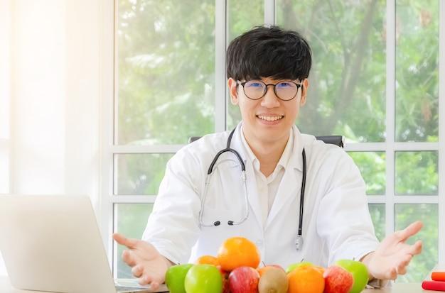 Portrait de souriant nutritionniste mâle asiatique avec des fruits biologiques frais en bonne santé dans son concept de bureau, de soins de santé et de régime Photo Premium