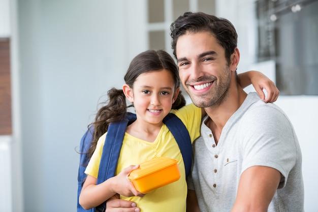 Portrait de souriant père et fille avec boîte à lunch Photo Premium