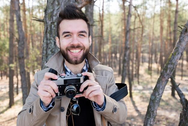 Portrait, de, a, souriant, randonneur mâle, tenant appareil photo, dans main, regarder appareil-photo Photo gratuit