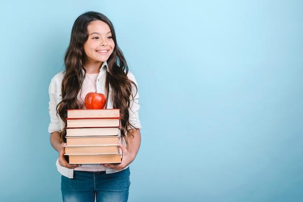 Portrait de souriante jeune fille nerd tenant pile de livres avec apple à ce sujet. retour à l'école. Photo Premium