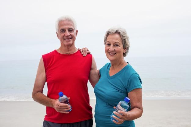 Portrait, de, sourire, couples aînés, tenant bouteille Photo Premium