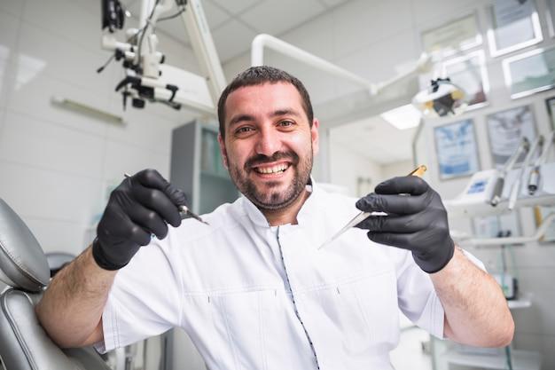 Portrait de sourire dentiste mâle avec des outils dentaires Photo gratuit