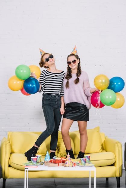 Portrait, sourire, deux, adolescentes, tenir, jaune, sofa, tenue, ballons colorés, dans main Photo gratuit