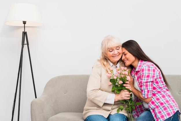 Portrait, sourire, fille adulte, embrasser, elle, heureux, mère aînée, tenant bouquet fleur Photo gratuit
