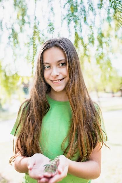 Portrait, sourire, fille, cheveux, tenue, brindille, mains, regarder appareil-photo Photo gratuit