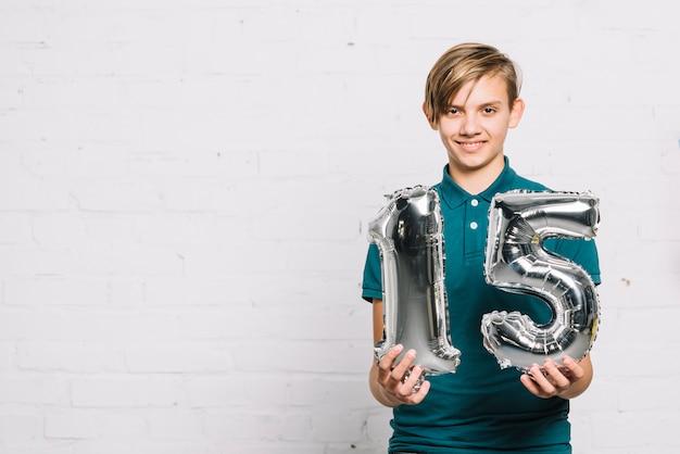 Portrait, sourire, garçon, projection, chiffre, ballon, feuille Photo gratuit