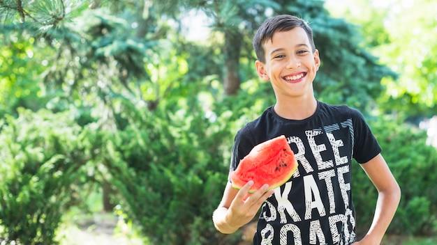 Portrait, de, sourire, garçon, tenue, tranche pastèque, dehors Photo gratuit