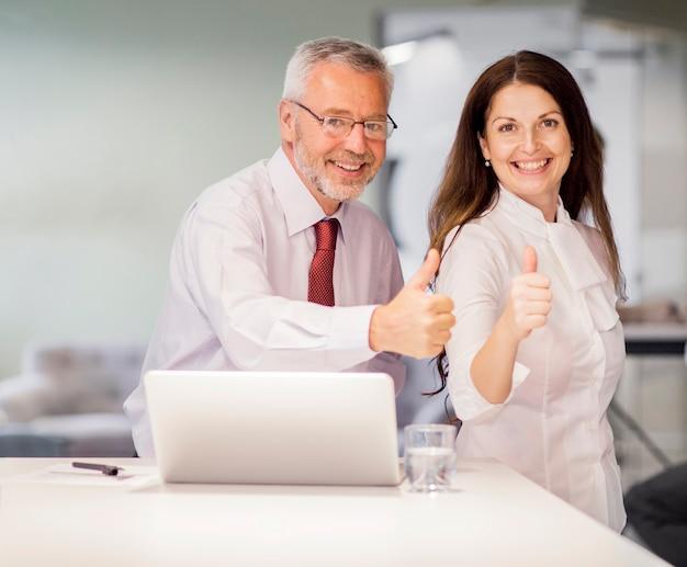 Portrait, sourire, homme affaires senior, et, femme affaires, projection, pouce haut, signe, dans, les, bureau Photo gratuit