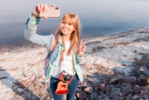 Portrait, de, a, sourire, jeune femme blonde, faire, geste paix, prendre, selfie, sur, téléphone portable Photo gratuit