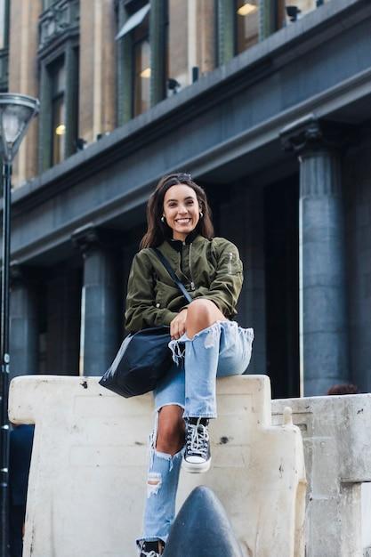 Portrait, de, a, sourire, jeune femme, séance, devant, bâtiment, à, sac, regarder appareil-photo Photo gratuit