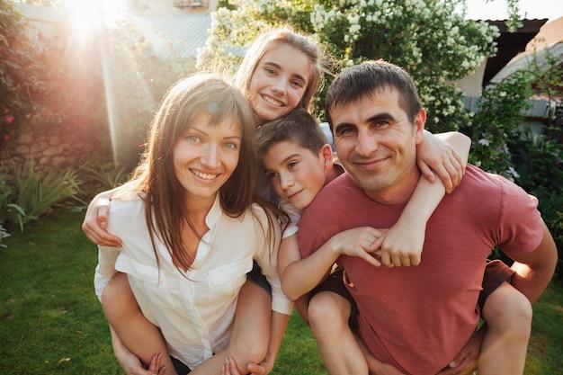 Portrait de sourire des parents avec leurs enfants au parc Photo gratuit