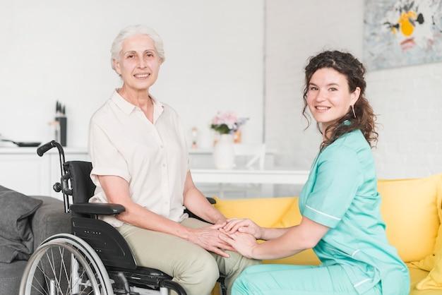 Portrait de soutien infirmière souriante avec senior patient féminin assis sur le sol Photo gratuit