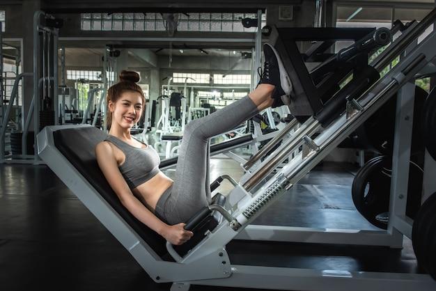 Portrait sport fille faisant la jambe appuie dans la salle de gym avec souriant concept de visage, de remise en forme et d'exercice. Photo Premium