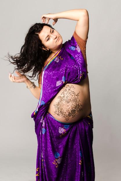 Portrait En Studio D'une Femme Enceinte Heureuse En Sari Indien, Un Ventre De Femme Enceinte Peint Au Henné Photo Premium