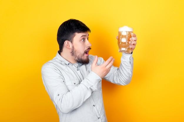 Portrait En Studio D'un Homme Surpris Qui Est Indigné Par La Qualité De La Bière, Sur Un Mur Jaune Photo Premium