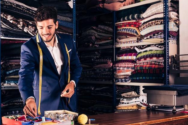 Portrait d'un tailleur masculin souriant travaillant dans son atelier Photo gratuit