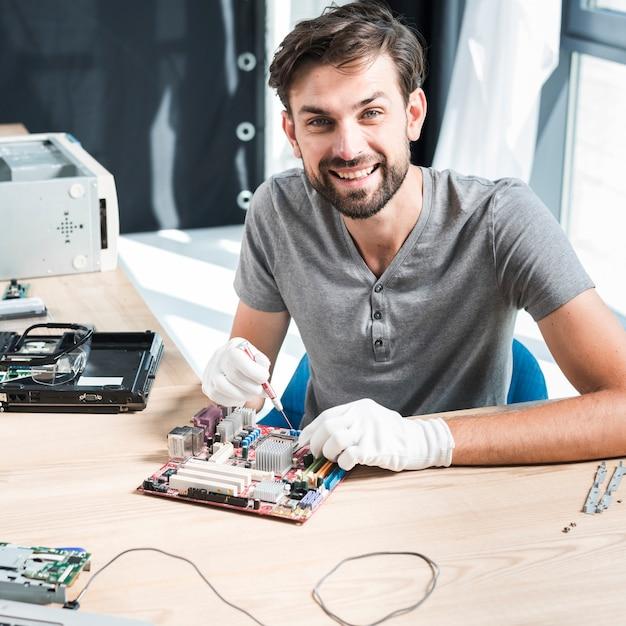 Portrait d'un technicien mâle souriant, réparation de carte mère d'ordinateur Photo gratuit